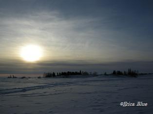 雪原を吹く風、ゆらぐ夕日