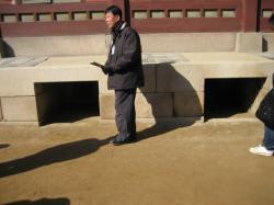 千秋殿のオンドル焚き口と説明してくださる日本語ガイドさん