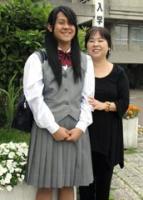 女子生徒の制服を着用してあこがれの開邦高校に入学した下里豪志さん(左)と母親の倫子さん=7日午後、南風原町新川の県立開邦高校