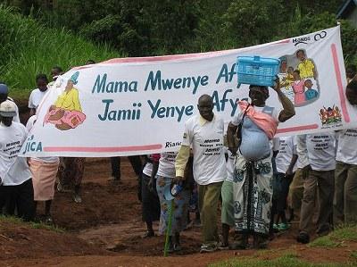 泥道をさっそうと行進するRiana HCスタッフとコミュニティ代表。先頭は妊婦体験ジャケットを着た男性(Riana HC)