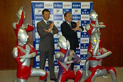 市役所の定例記者会見でポーズをとる、中田市長と円谷会長