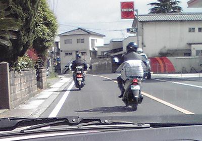 車が来ても道路の真ん中を走り続ける原付バイク