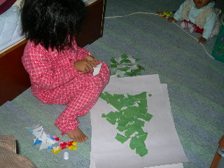 Pasting peaces of green papers made of calender for making X'mas tree.