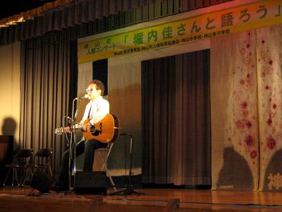 神山人権コンサート(草木染めの幕をバックに歌うkeiさん)
