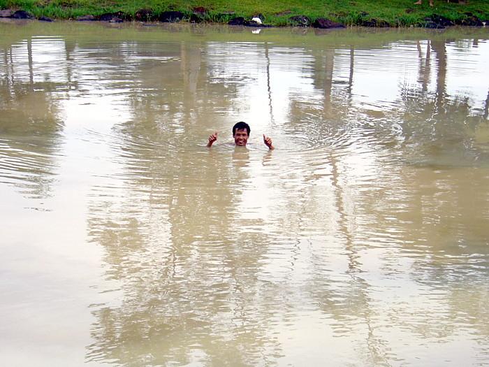 プレーヤーが池に打ち込んだボールを捜す現地人